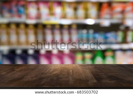 image of wooden table in front of abstract blurred background of super market. can be used for display or montage your products.Mock up for display of product