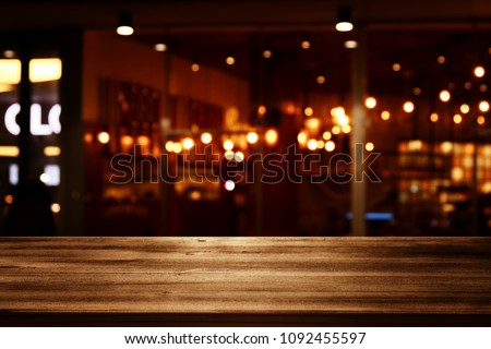 Image of wooden table in front of abstract blurred restaurant lights background #1092455597