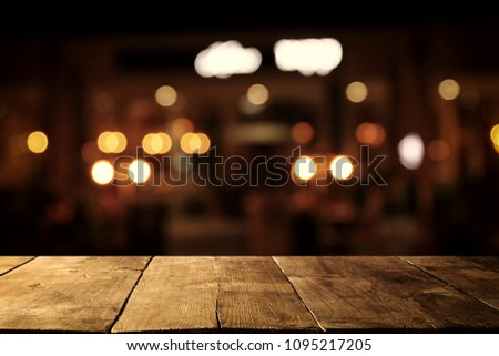 Image of wooden table in front of abstract blurred restaurant lights background #1095217205