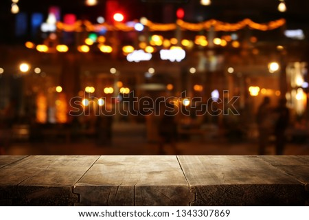 Image of wooden table in front of abstract blurred restaurant lights background #1343307869