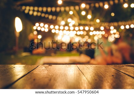 Image of wooden table in front of abstract blurred restaurant lights background #547950604
