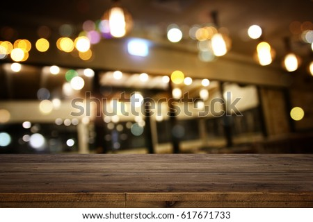 Image of wooden table in front of abstract blurred restaurant lights background. #617671733