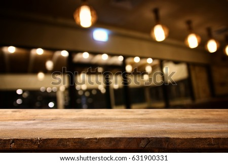 Image of wooden table in front of abstract blurred restaurant lights background. #631900331