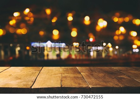 Image of wooden table in front of abstract blurred restaurant lights background. #730472155