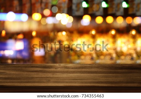 Image of wooden table in front of abstract blurred restaurant lights background. #734355463