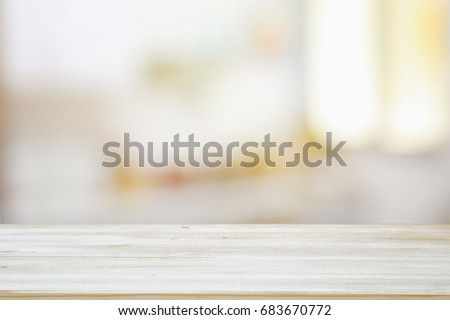 image of wooden table in front of abstract blurred window light background.