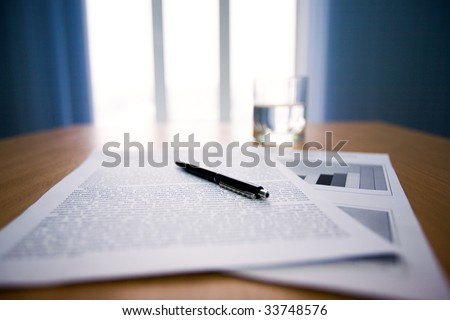 Image of workplace with focus on papers and pen on the table