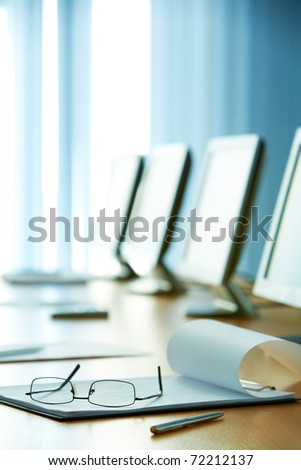 Image of workplace with paper, eyeglasses and monitors near by