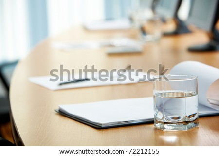 Image of workplace with paper, glass of water and monitors near by