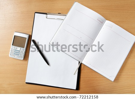Image of workplace with paper, notepad, pen and palmtop gadget on it
