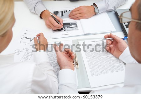 Image of workteam working with documents at business meeting