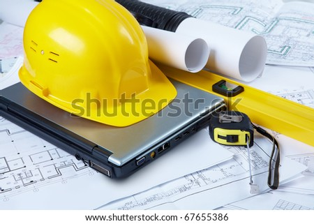 Image of yellow helmet over laptop with ruler placed on blueprint of house