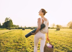 Image of yoga inspiration on nature. Young woman with yoga mat gets ready to practicing yoga outdoor. Beautiful female with slim, strength body in white clothes. Healthy and conscious lifestyles.
