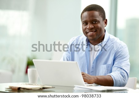 Image of young African businessman looking at camera at workplace - stock photo