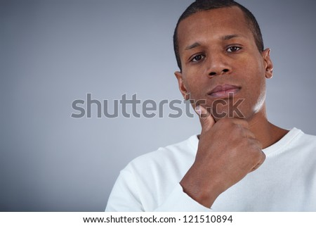 Image of young African man looking at camera with pensive expression