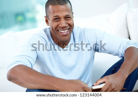 Image of young African man looking at camera with smile
