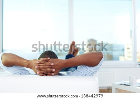 Image of young African man lying on sofa and having rest