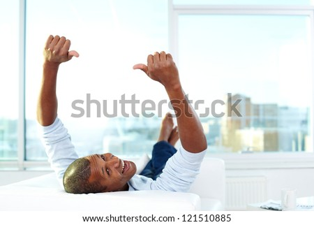 Image of young African man lying on sofa with thumbs up and looking at camera