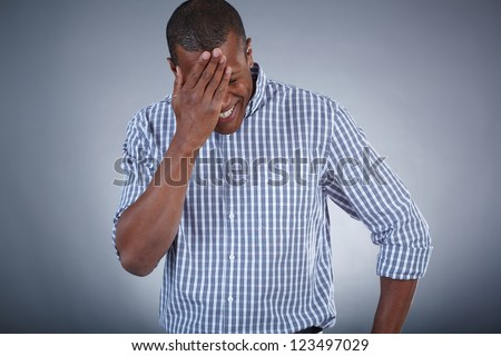 Image of young African man touching his head in surprise