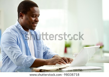 Image of young African man typing on laptop