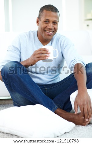 Image of young African man with cup sitting on the floor and looking at camera