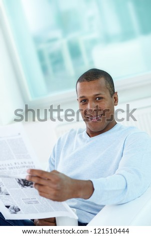 Image of young African man with newspaper looking at camera