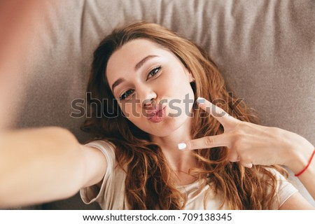 Image of young amazing emotional pretty lady lies on sofa indoors. Looking camera make selfie make peace gesture.