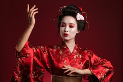 Image of young asian geisha woman in traditional japanese kimono dancing isolated over red background