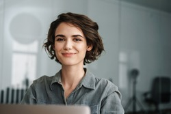 Image of young beautiful joyful woman smiling while working with laptop in office