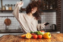 Image of young beautiful woman listening to music on mobile phone while cooking fresh vegetables salad in kitchen interior at home