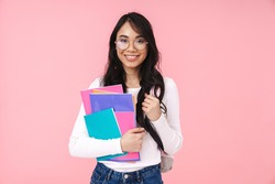 Image of young brunette asian student girl wearing eyeglasses holding paper folders isolated over pink background