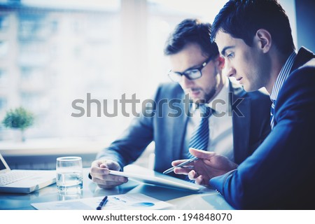 Image of young businessman pointing at touchpad while explaining his idea to colleague at meeting - Shutterstock ID 194848070