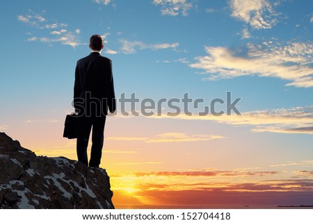 Image of young businessman standing on top of hill