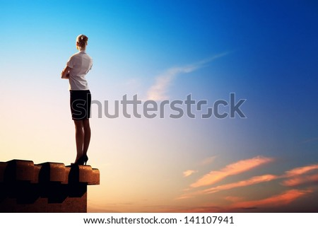 Image of young businesswoman standing on top of building