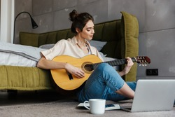 Image of young caucasian brunette woman sitting on floor and playing acoustic guitar at home