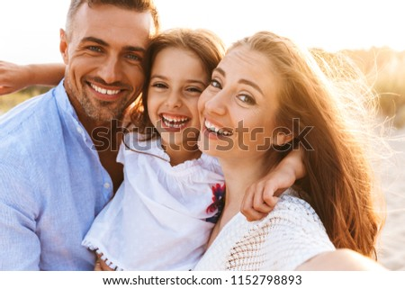 Image of young cute parents having fun together outdoors at the beach with their daughter. Looking camera.