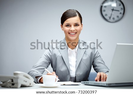 Image of young employer looking at camera while planning work in office