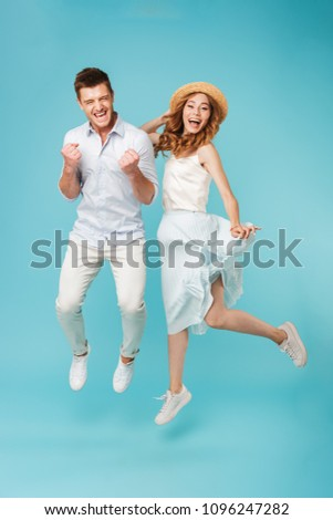 Image of young excited caucasian people man and woman jumping isolated over blue background make winner gesture screaming. #1096247282