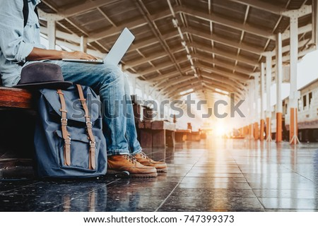 Image of Young freelance working at train station before travel. work and travel concept.