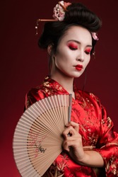 Image of young geisha woman in traditional japanese kimono holding wooden hand fan isolated over red background