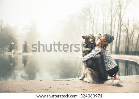 Image of young girl with her dog, alaskan malamute, outdoor