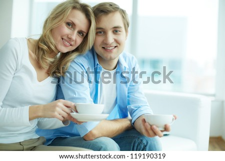 Image of young guy and his girlfriend looking at camera while having tea