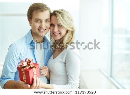 Image of young guy and his girlfriend with giftbox looking at camera