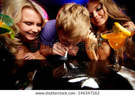 Image of young guy sniffing cocaine surrounded by two girls in night club