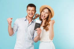Image of young happy caucasian loving couple isolated over blue background holding passport with tickets make winer gesture.