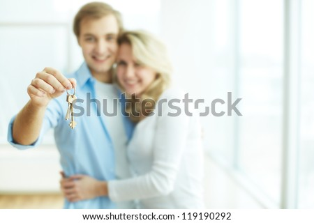 Image of young happy couple embracing while man showing key from new flat