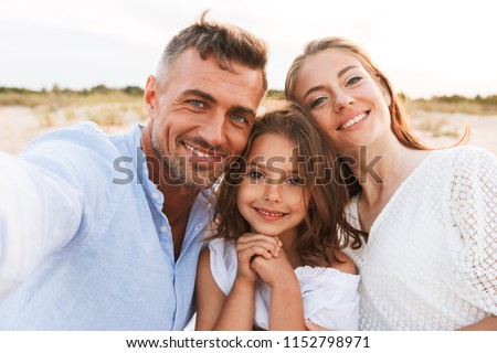 Image of young happy family outdoors at the beach take a selfie by camera.