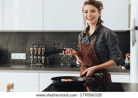 Image of young happy lady standing in kitchen while cooking fish. Looking at camera.