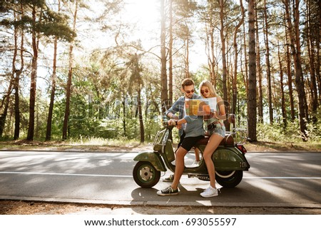 Image of young happy loving couple holding map outdoors near scooter. Looking aside.