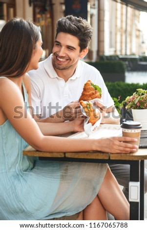 Image of young happy loving couple sitting in cafe outdoors while talking with each other eating croissants.